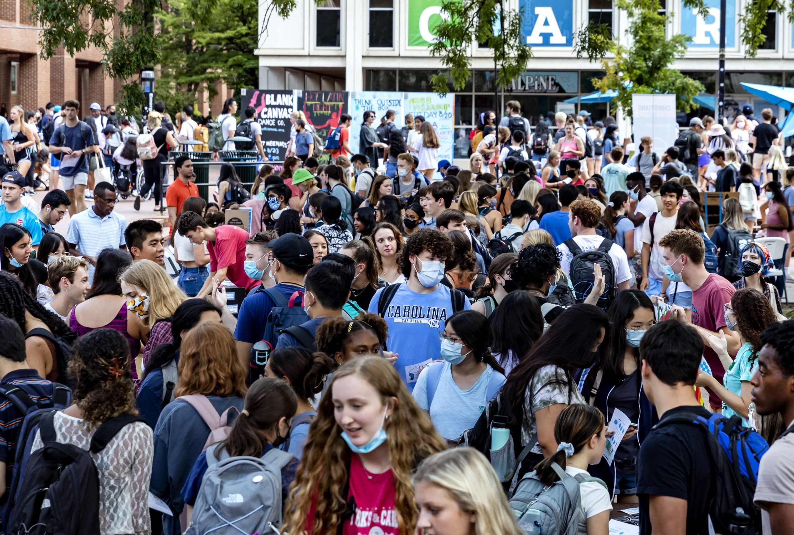 UNC campus scene. Students meet in front of the bookstore in large groups. Multiple are seen wearing masks.