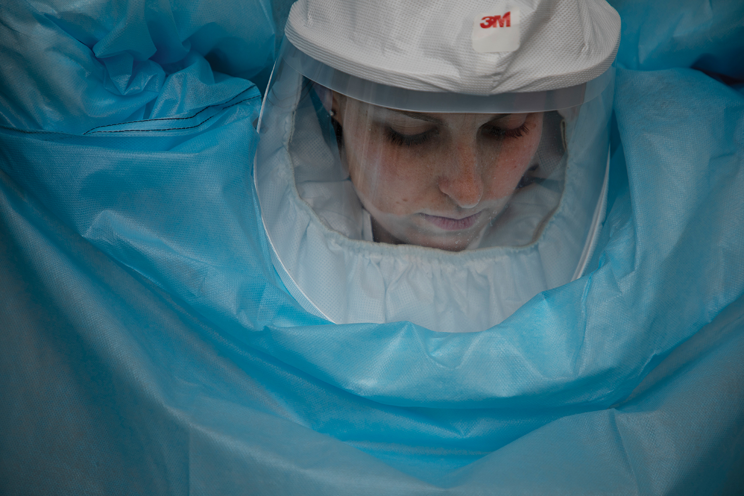 A researcher puts on their full N95 gear, complete with gown, face shield, and head gear.