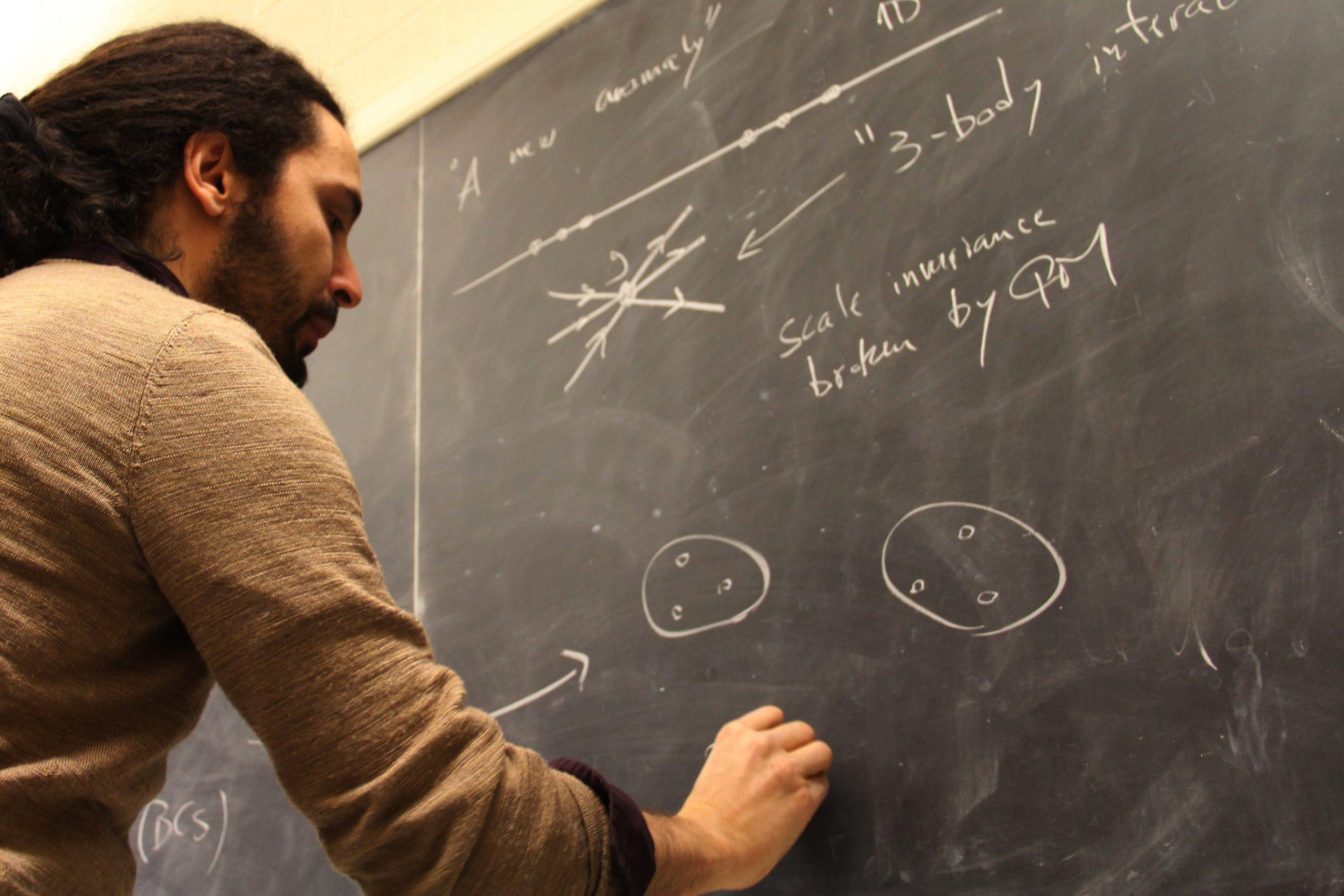 Professor writes on a black board.