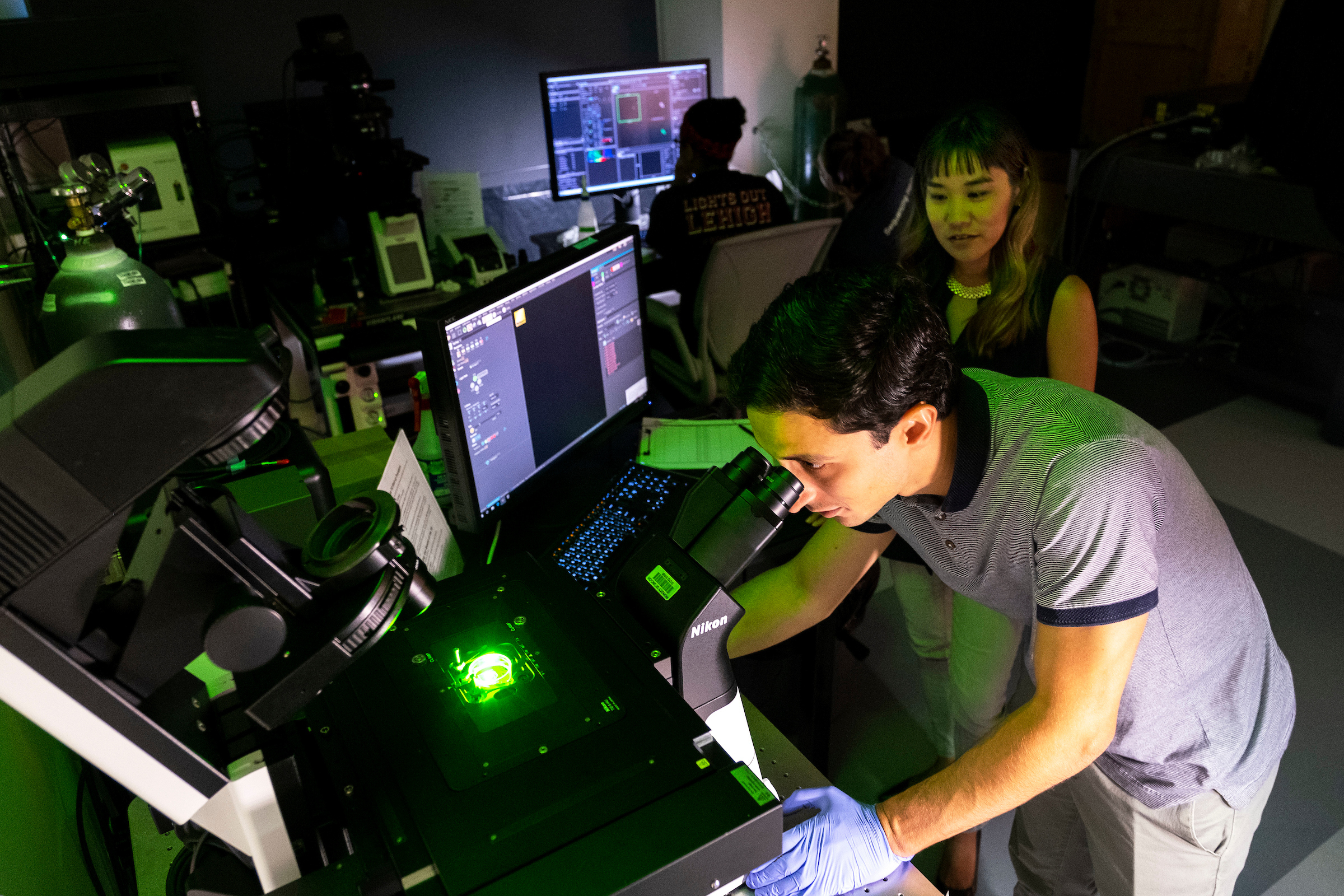 Researchers look through microscopes at a large computer setup.