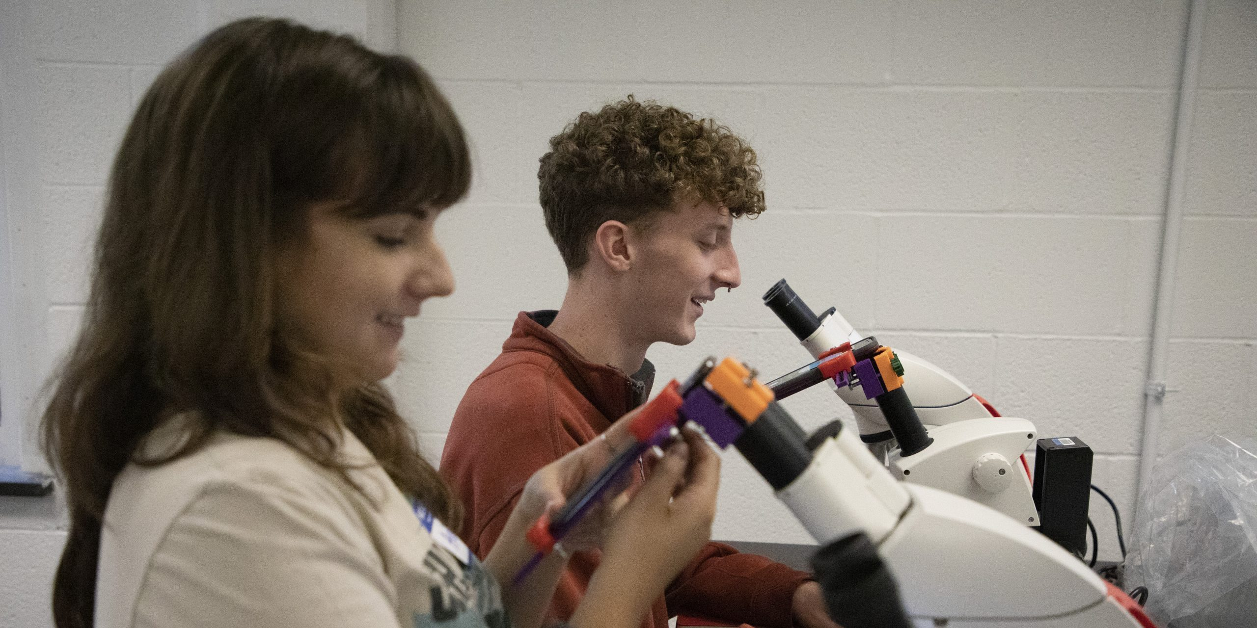 Two students smile as they look into table top microscopes.