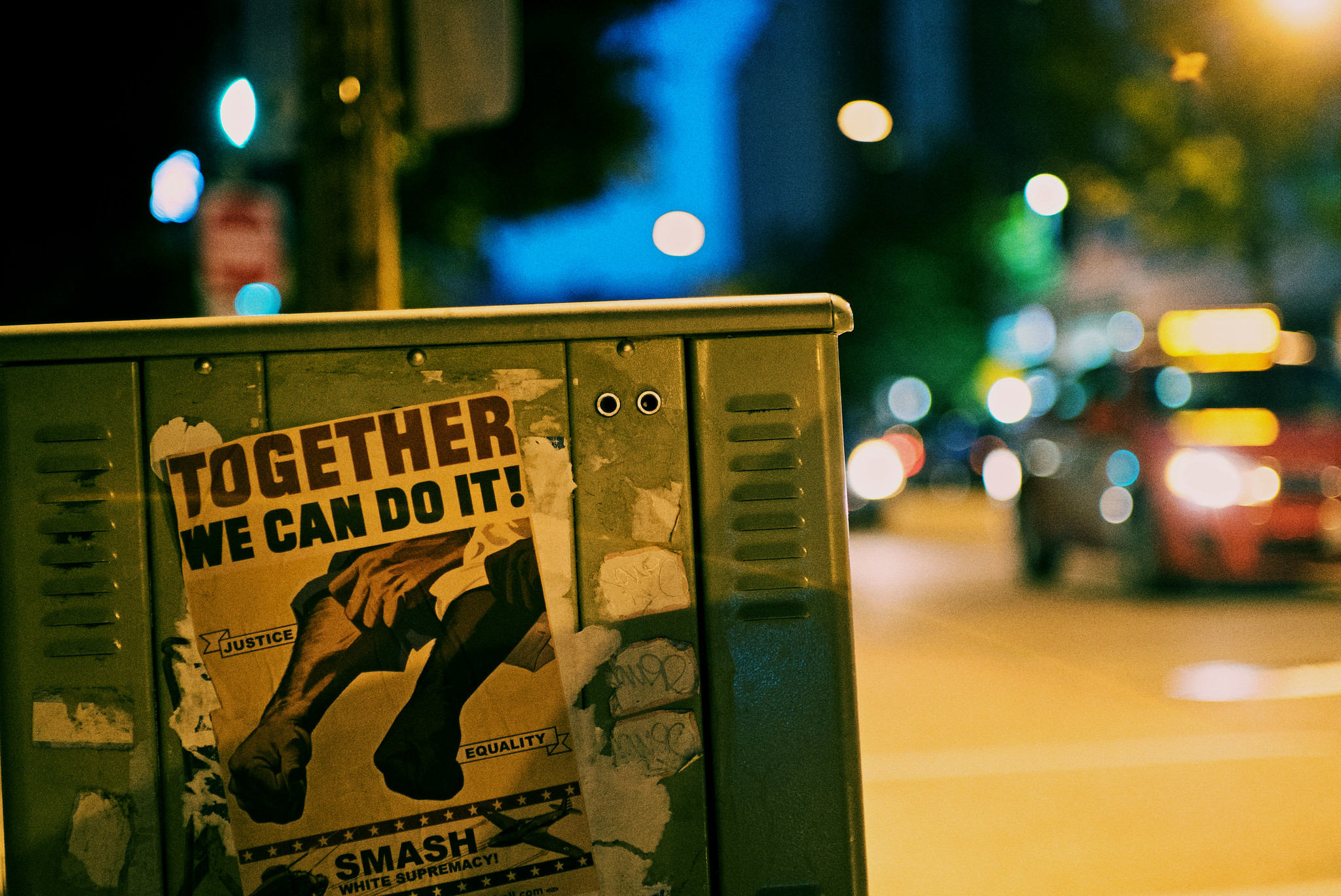 """Night time photo of a technical box on a sidewalk with a Black Lives Matter poster that reads """"Together, we can do it! Smash White Supremacy."""""""