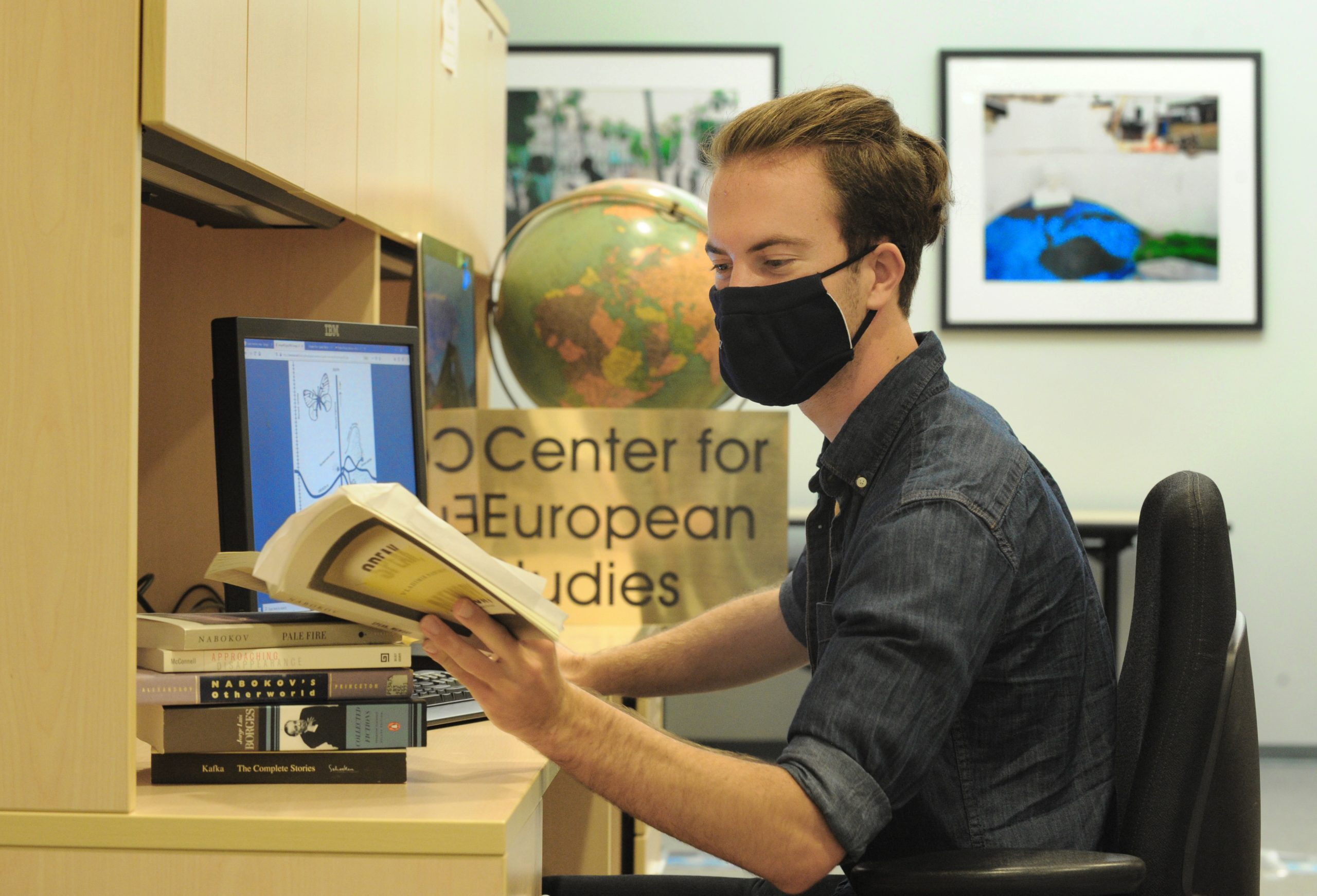Student, in a mask, reads a book while at a computer.