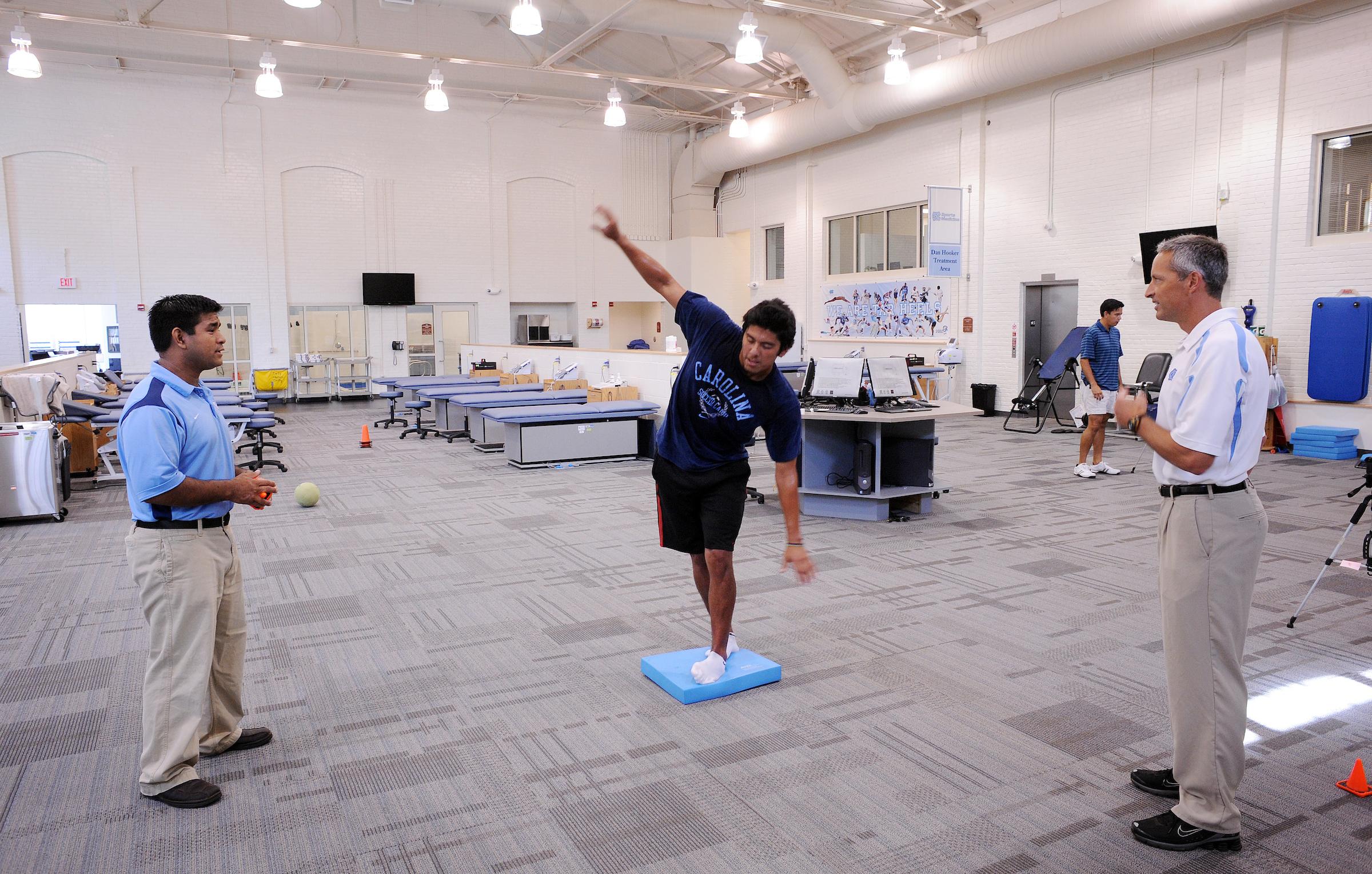 Researchers watch as a test subject balances on a small blue mat.